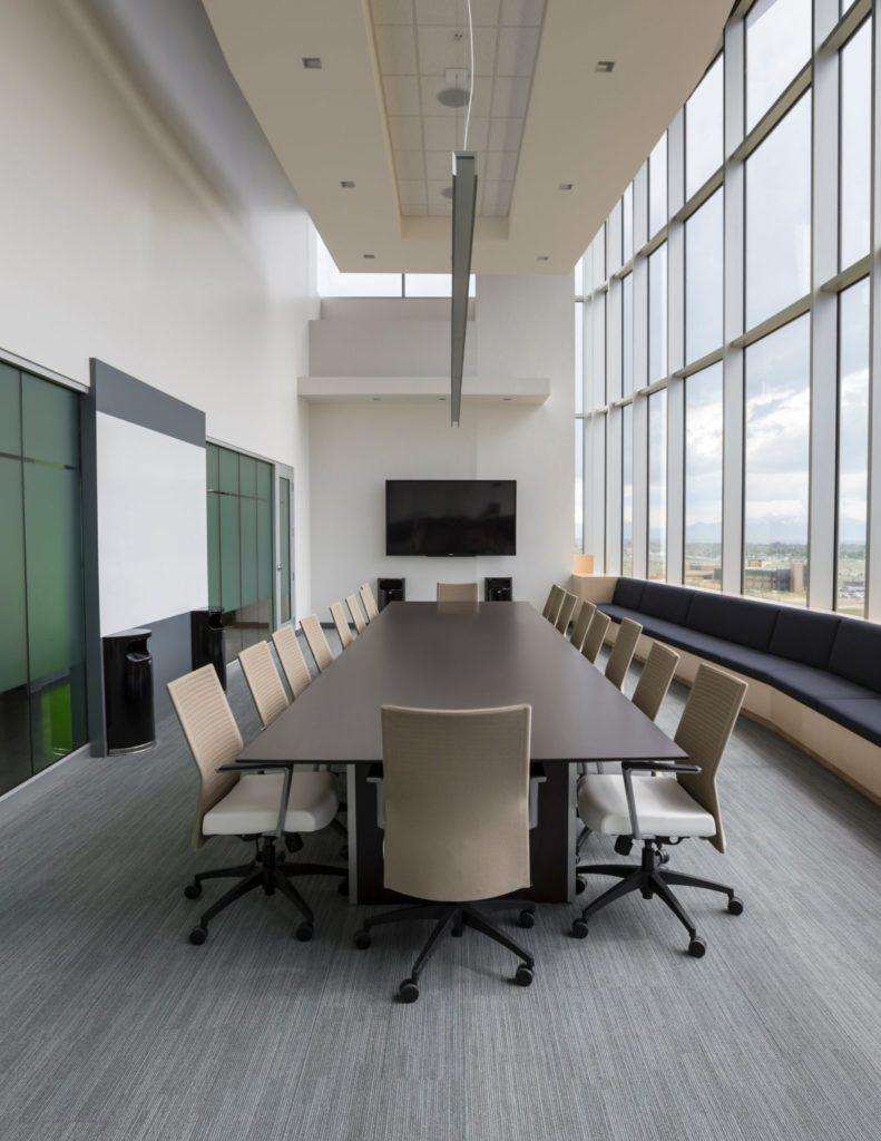 Interieurfoto vergaderkamers kantoor Rotterdam - moderne bruine houten vergadertafel met 18 beige vergaderstoelen in hoge ruimte