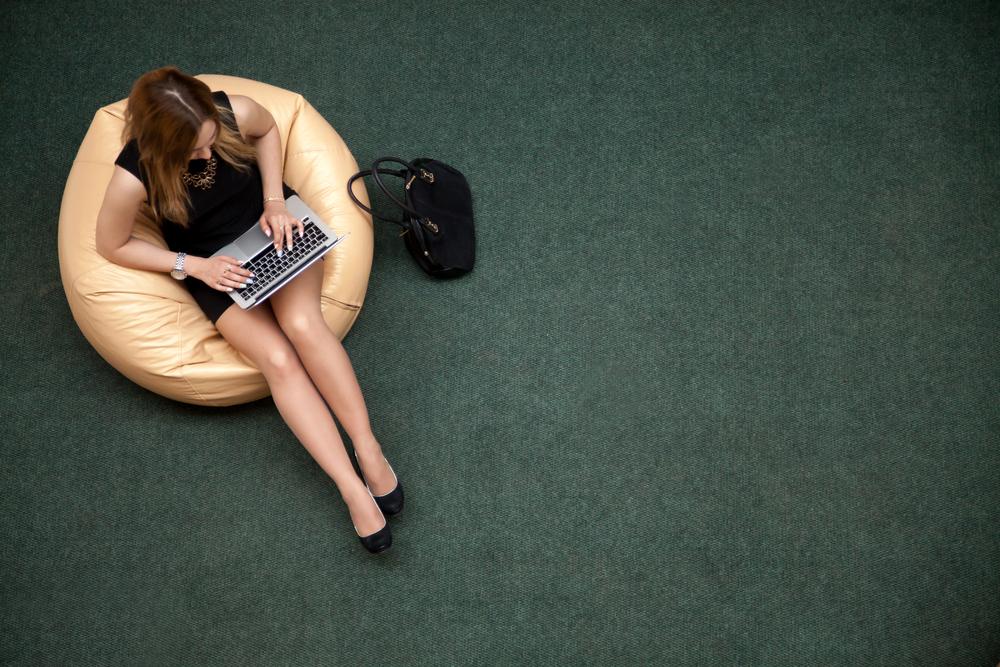 zittende jonge dame met laptop op poef